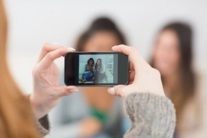 Close up of a woman photographing friends with smartphone