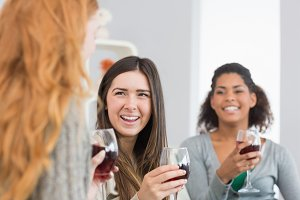 Cheerful friends with wine glasses enjoying a conversation at home