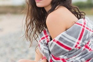 Serious woman covered with blanket at beach