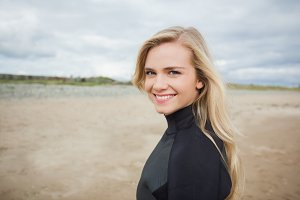 Beautiful woman in wet suit at the beach