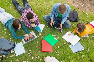 College students using laptop while doing homework in park