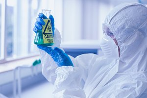 Scientist in protective suit with hazardous chemical in flask at lab
