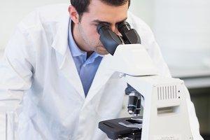 Male scientific researcher using microscope in lab