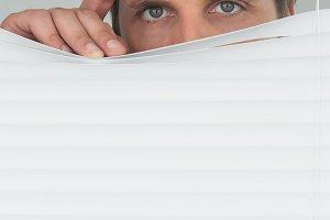 Green eyed businessman peeking through blinds