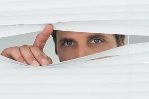 Closeup of green eyed businessman peeking through blinds