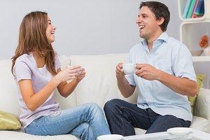 Cheerful couple enjoying their tea at home
