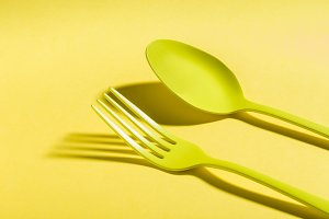 Yellow spoon and fork on yellow background