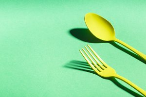 Yellow spoon and fork on green background