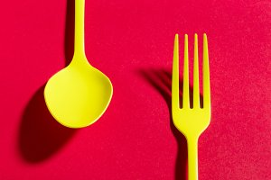 Yellow spoon and fork on red background