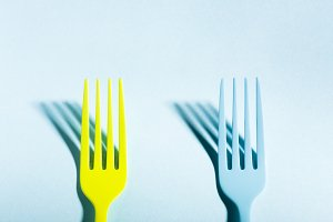 Yellow and blue forks on blue background