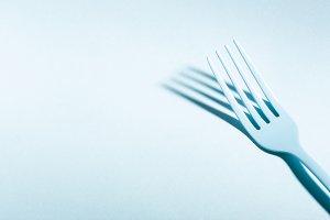 Blue fork on blue background
