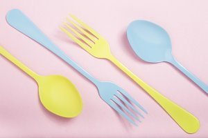 Yellow and blue cutlery on pink background