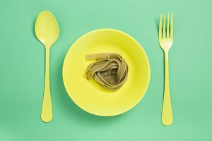 Vegetable tagliatelle on a yellow plate on a green background