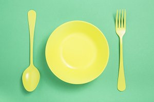 Plate and cutlery yellow on green background