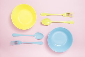 Yellow and blue plates and silverware on a pink background