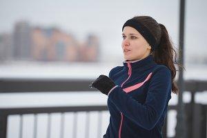 Young caucasian woman fitness model running at snow winter promenade, close up