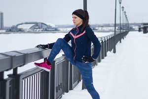 Fitness girl with pink sneakers doing stretching outside at snow winter day, sport concept