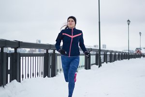 Young caucasian woman fitness model running at snow winter promenade