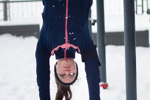 Young sport woman hanging upside down - strength exercises on work out fitness at snow winter park