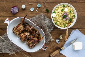 Delicious fried quails with eggs with bulgur porridge on a wooden table, rustic style. Top view