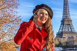 woman on embankment near Eiffel tower talking on smartphone