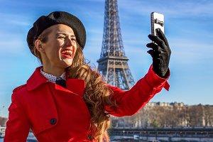 woman on embankment near Eiffel tower in Paris taking selfie