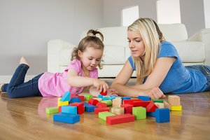 Mother and daughter playing with building blocks on floor