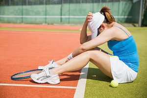 Upset tennis player sitting on court