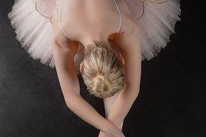 Graceful ballerina bending forward in pink tutu