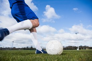 Football player in blue about to kick ball