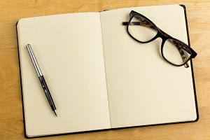 Overhead of open notebook with pen and glasses