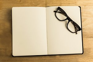 Overhead of reading glasses with notebook