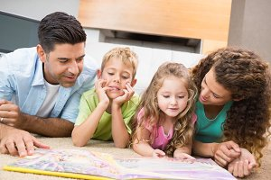 Cute siblings lying on the rug reading storybook with their parents