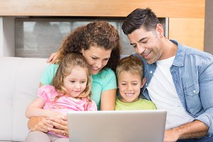 Happy family sitting on sofa using laptop together