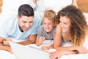 Smiling young family using laptop together on bed