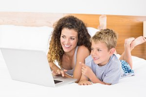 Cheerful blonde boy and mother lying on bed using laptop