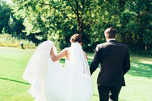 Young couple walk on green field. Bride and groom happy