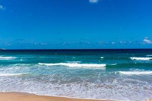 Australian ocean beach with people bathing. Cronulla beach, NSW. Summer ocean beach with surf and people enjoying water activities.