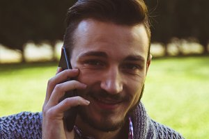 Young man hipster talking on mobile phone