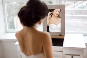 Portrait of the young beautiful bride looks at herself in the mirror