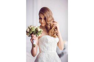 Beautiful bride with wedding bouquet indoors. Wedding fashion