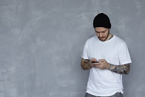 Stylish guy in white t-shirt, black hat with mobile. Brutal tattoo man use pphone for surfing internet or talk with friends. Communication concept in studio.