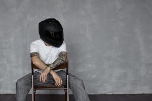 Biker concept. Tattooed man in black helmet and white t-shirt on chair. Brutal and strong person. Motorbicycle life. Strong and brave bike rider.