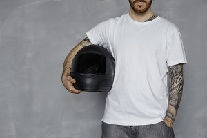 Motorbiker concept with blank white t-shirt. Brutal bearded man with tattooed arms keep black motorcycle helmet on neutral grey background in studio. Extreme reder life.