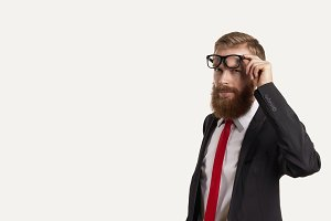 Portrait of thinking businessmen in dark suit, white shirt, red tie. Man with red beard and hair keep eye glasses by one hand. Free space for advertising or promotional content.