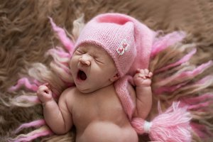 Sweet newborn in cap yawns