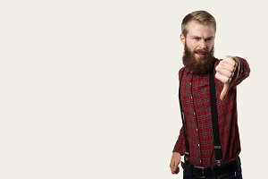 Stylish hipster with big beard and red shirt show dislike on neutral background. Disgust emotion on the face. Copy space for advertising text od promotional goods.