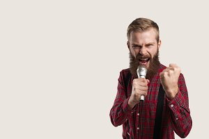 Portrait of rant person with microphone. Man sing the rock. Aggressive bearded face. Copy space for advertising. American guy in red shirt and suspenders.