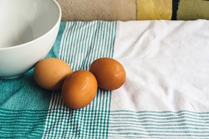 Eggs and bowl on tablecloth
