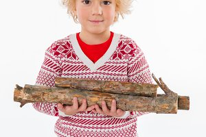 child standing with firewood